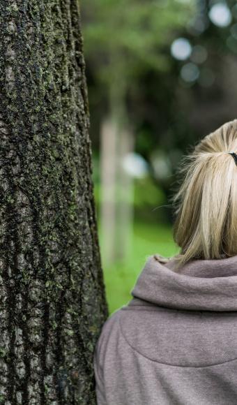 Frau an Baum angelehnt, Titelbild Studierende mit psychischen Erkrankungen